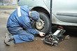 machanic repairman at tyre fitting with car jack