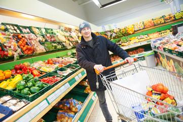 man choosing vegetables in supermarket store