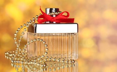 Perfume bottle with red bow on yellow background