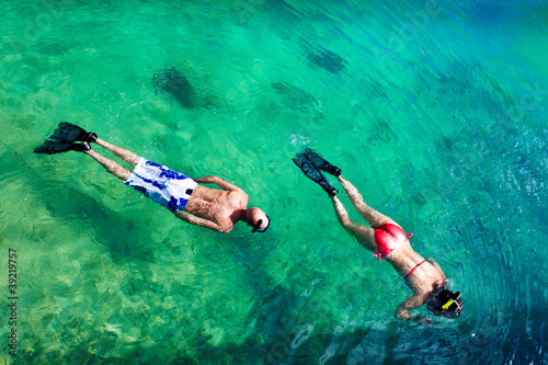 Young couple snorkeling in clean water over coral
