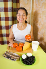 Woman with food products for farci tomato salad