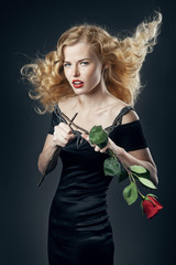 Beautiful girl in black dress with broken rose