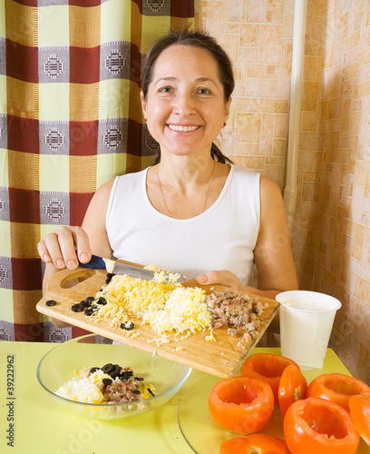 Woman making stuff  for  farci tomato salad