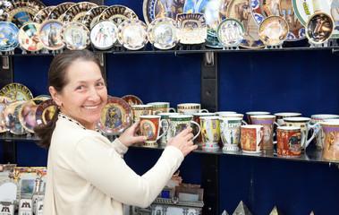 tourist  chooses souvenir cup in egyptian shop