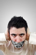 Angry young man having gray duct tape on his mouth