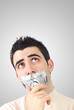 Curious young man having gray duct tape on his mouth