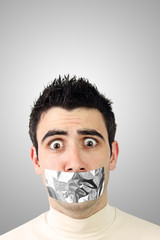 Scared young man having gray duct tape on his mouth