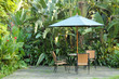 Garden furniture - rattan chairs and table under umbrella on a w