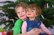 brother and sister in front of christmastree