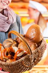 Female customer with breadbasket in bakery