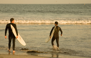 Two surfers on a warm summer day at the beach.