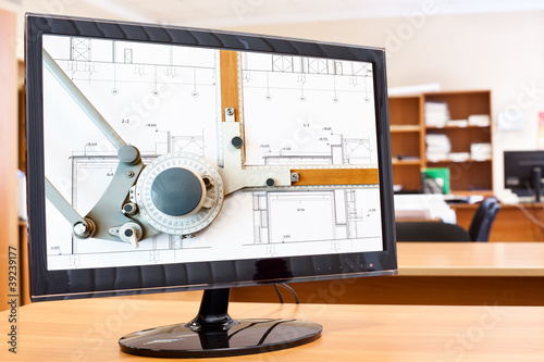Computer monitor with blueprints and drawing board on desktop