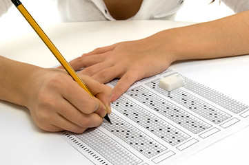 Student filling out answers to a test with a pencil