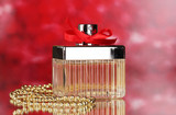 Perfume bottle with red bow on red background