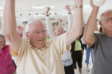 Senior people exercising with dumbbells