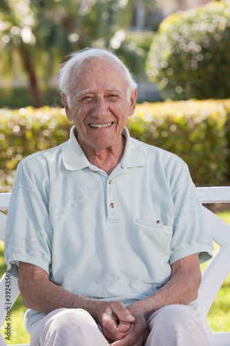 Portrait of a senior man sitting on a park bench and smiling
