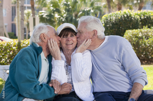 Two senior men kissing their female friend in a park