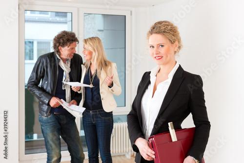 Paar bei  Besichtigung einer Wohnung mit Maklerin
