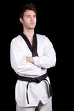 Young martial arts man standing on black background