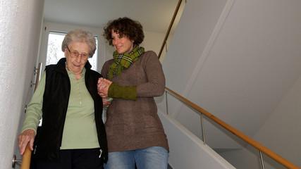 älter Damen beim treppensteigen mit Betreuerin