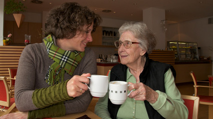 Seniorin und junge Frau beim Kaffee trinken