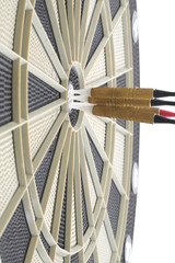 Many darts in bulls eye of dartboard