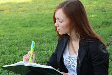 Redhead woman sitting on the grass, reading a book