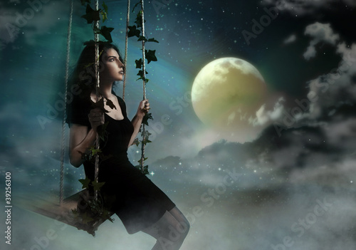 Leinwandbild Motiv Beauty brunette swinging in night heaven