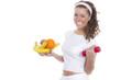 Lachende junge Frau mit Früchten und einer roten Hantel
