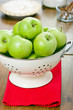 Green apples in a colander.