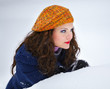 Young woman hiding in snow