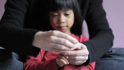 Mother Trimming Little Girls Fingernails