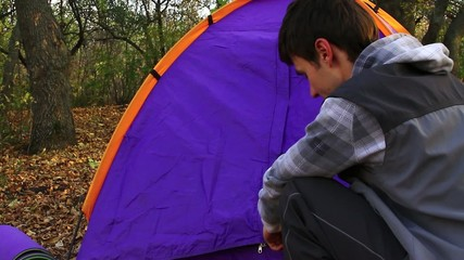 Young man pitching a tent looks at girl