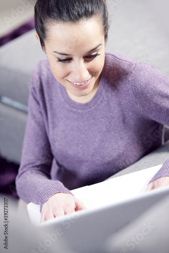 at home: young woman working on her laptop