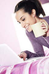 Happy casual  young lady using laptop while lying in bed