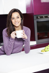 Beautiful young  woman having coffee while at the kitchen