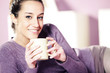 Portrait of a pretty happy young woman holding a cup of coffee i