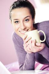 Portrait of a pretty happy young woman holding a cup of coffee