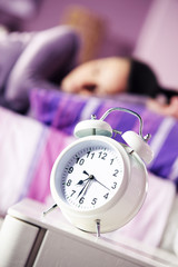 An alarm clock with a sleeping young woman in the background