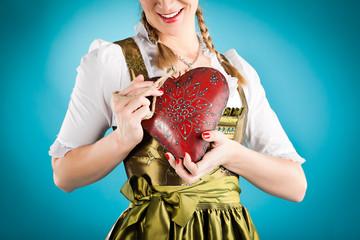 Junge Frau in Dirndl mit Herz in Liebe