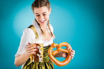 Junge Frau in Dirndl mit Bier und Bretzel