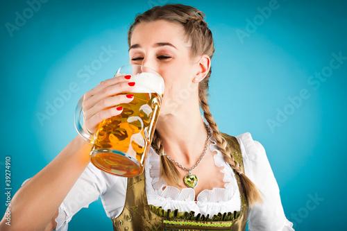 Junge Frau in Tracht trinkt Bier