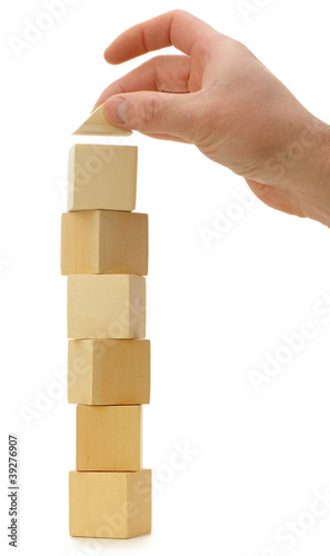 The hand establishes a toy roof on wooden cubes
