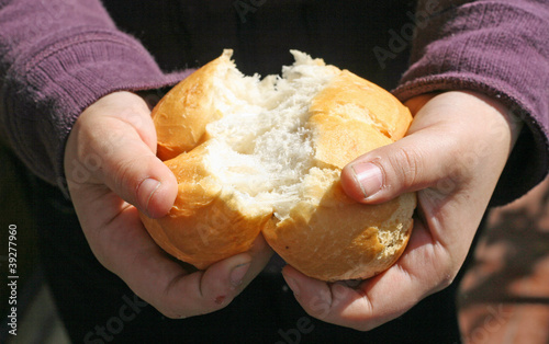 child who breaks a piece of bread with hands