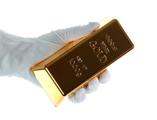 gold bar in hand with white glove