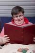 Geistig behinderte Frau liegt im Sessel und liest