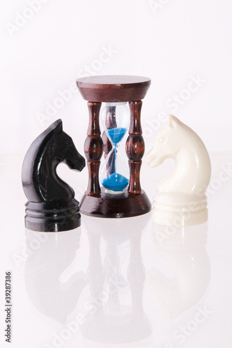 Two chess horses with sand-clock