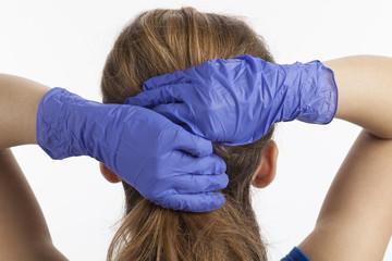 Frau greift sich mit blau behandschuhten Händen in die Haare