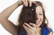 Frau fotografiert lächelnd mit alter Kamera