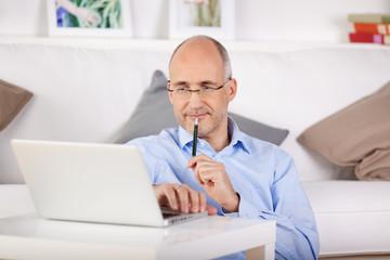 zufriedener mann sitzt zuhause am laptop